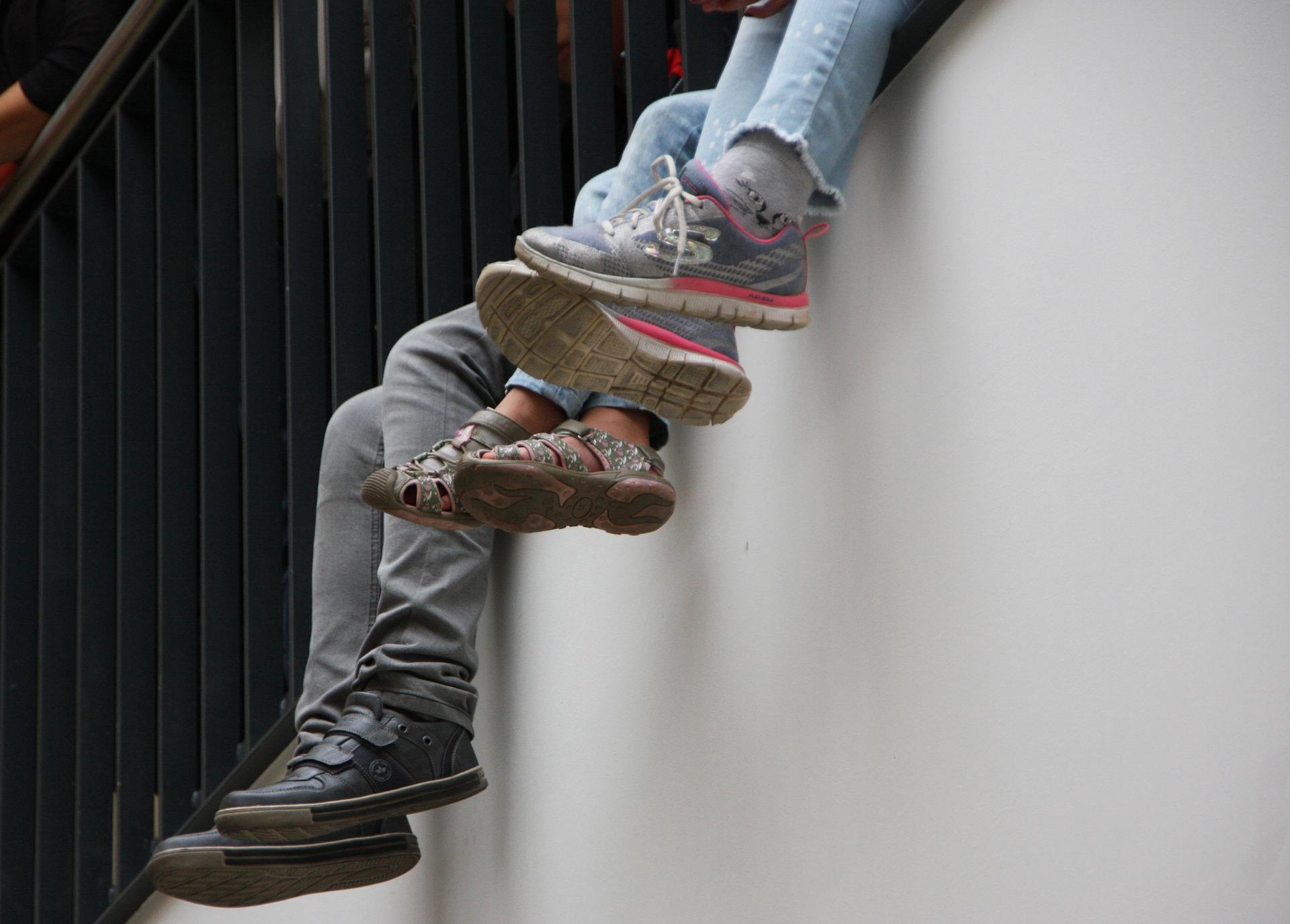 legs dangling off a wall